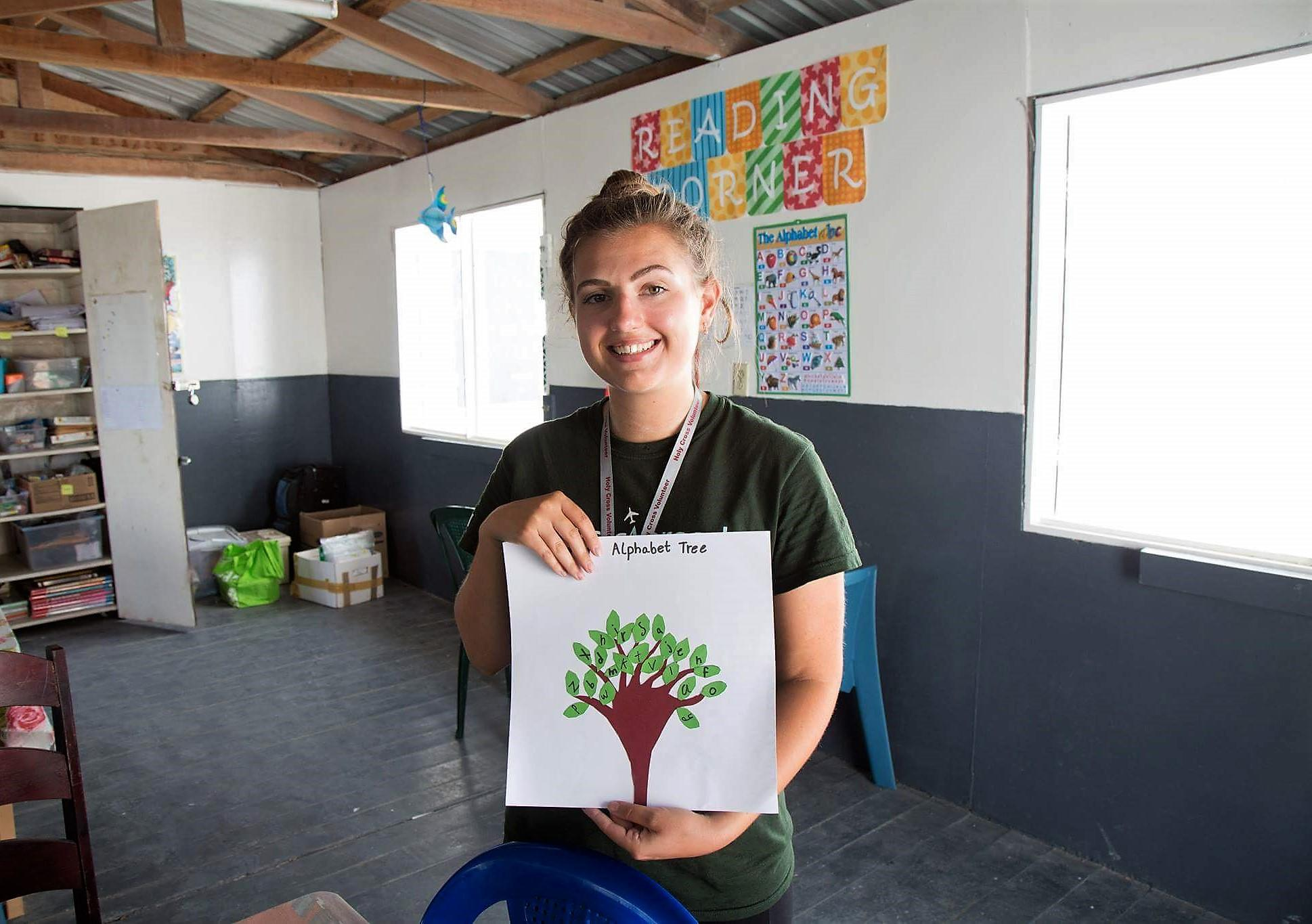 Projects Abroad volunteer holds up an alphabet tree created by one of her students at her Teaching placement in Belize